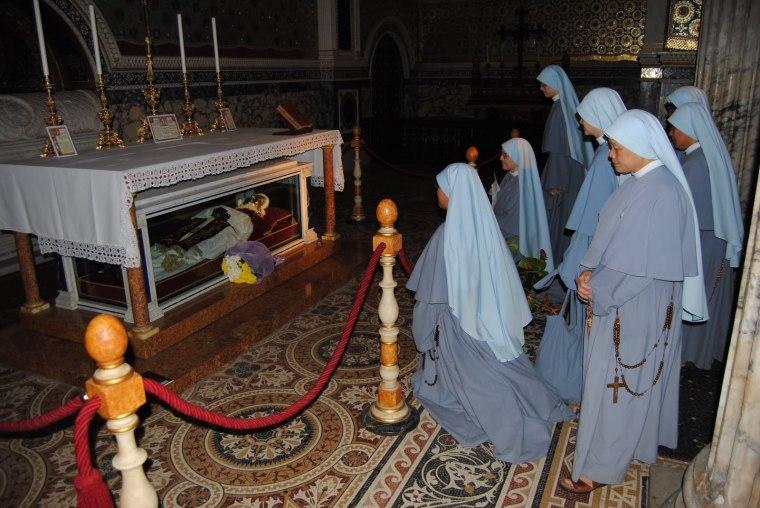 Le suore francescane dell'Immacolata ritratta in preghiera davanti alla tomba di Papa San Pio X.